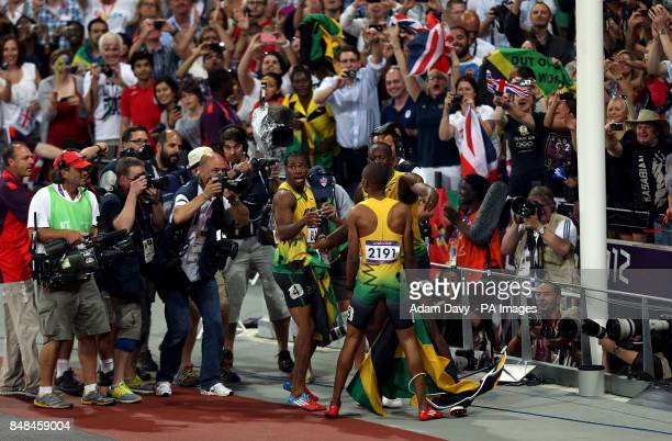 Jamaica's Usain Bolt celebrates with his teammates Yohan Blake and Warren Weir in front of photographers after winning the Men's 200m Final at the...
