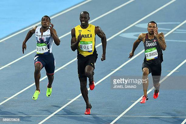 TOPSHOT Jamaica's Usain Bolt competes with Britain's Chijindu Ujah and Canada's Andre De Grasse in the Men's 100m Semifinal during the athletics...