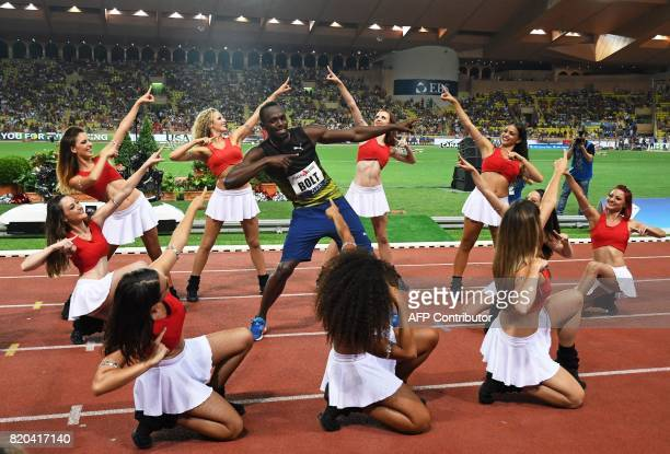 Jamaica's Usain Bolt dances with pompom girls as he celebrates winning the men's 100m event at the IAAF Diamond League athletics meeting in Monaco on...