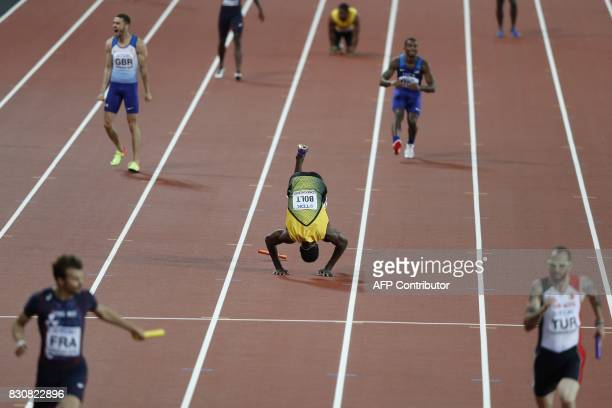 TOPSHOT Jamaica's Usain Bolt does a forward roll as he pulls up injured in the final of the men's 4x100m relay athletics event at the 2017 IAAF World...