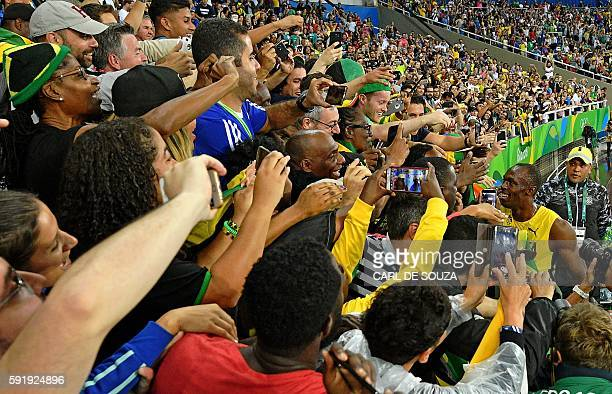 TOPSHOT Jamaica's Usain Bolt greets fans as he celebrates after winning the Men's 200m Final during the athletics event at the Rio 2016 Olympic Games...