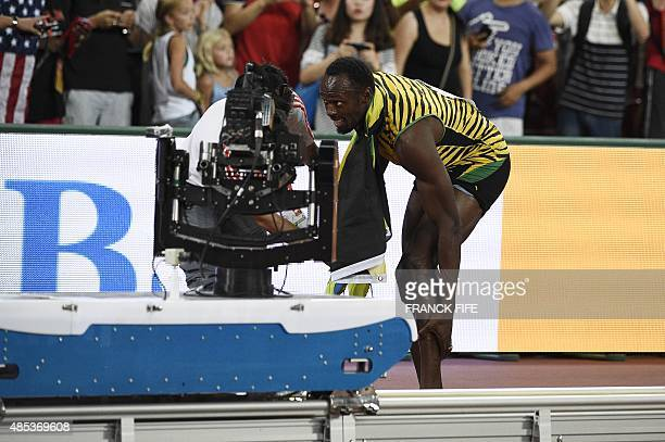 Jamaica's Usain Bolt holds his ankle after a cameraman on a segway crashed into him in the final of the men's 200 metres athletics event at the 2015...