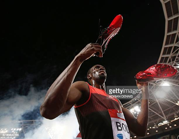 Jamaica's Usain Bolt holds out his spikes after as he interacts with spectators after winning the men's 200m at the IAAF Diamond League Anniversary...