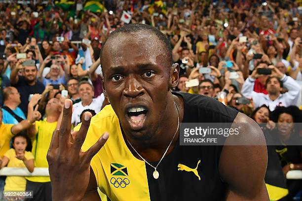 TOPSHOT Jamaica's Usain Bolt holds up three fingers for a third relay Olympic title after Team Jamaica won the Men's 4x100m Relay Final during the...
