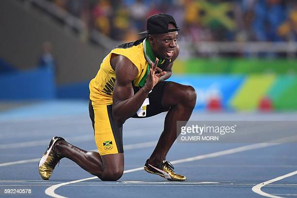 Jamaica's Usain Bolt holds up three fingers for a third relay Olympic title after Team Jamaica won the Men's 4x100m Relay Final during the athletics...