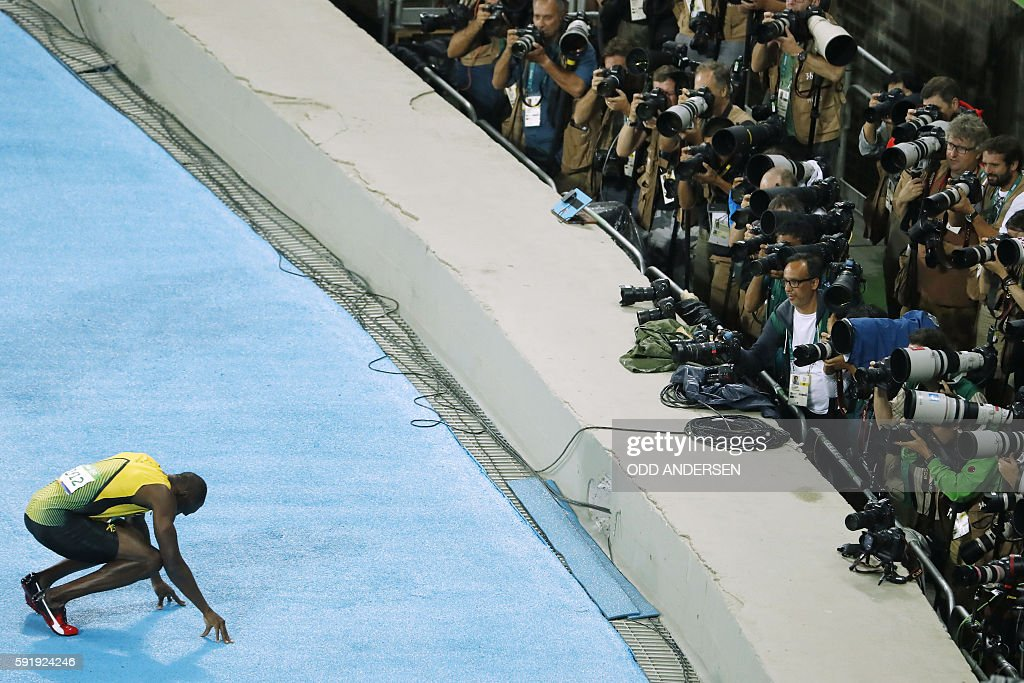 TOPSHOT - Jamaica's Usain Bolt kneels on the track in front of photographers as he celebrates after winning the Men's 200m Final during the athletics event at the Rio 2016 Olympic Games at the Olympic Stadium in Rio de Janeiro on August 18, 2016. / AFP / Odd ANDERSEN