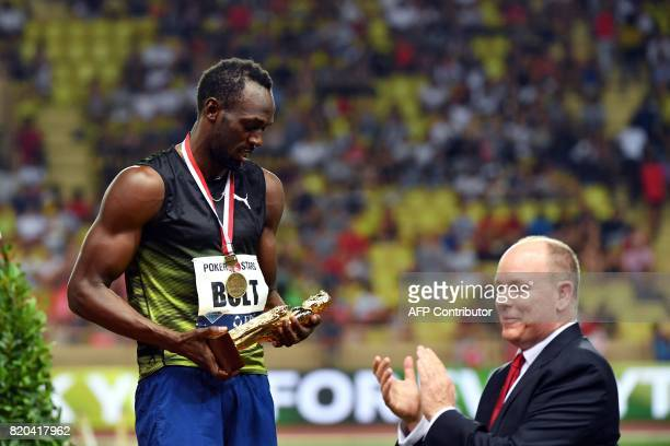 Jamaica's Usain Bolt looks at his trophy flanked by Prince Albert II of Monaco after winning the men's 100m event at the IAAF Diamond League...