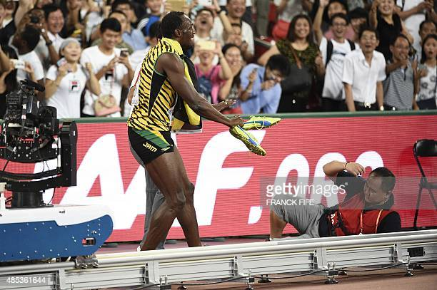 Jamaica's Usain Bolt reacts after a cameraman on a segway crashed into him during his celebrations after the final of the men's 200 metres athletics...