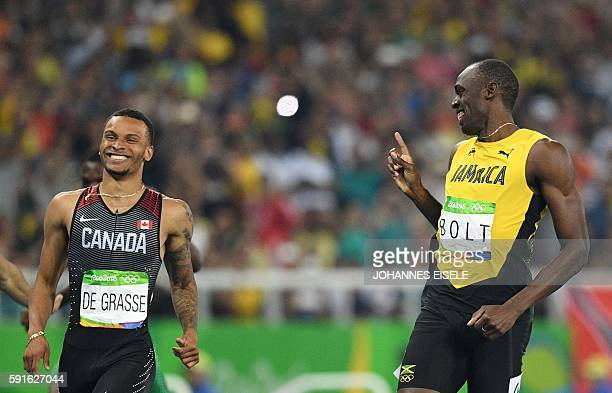 TOPSHOT Jamaica's Usain Bolt shares a laugh with de Canada's Andre De Grasse after their Men's 200m Semifinal during the athletics event at the Rio...