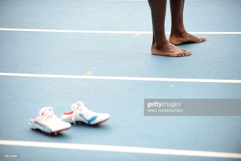 Jamaica's Usain Bolt stands next to his trainers after Jamaica won the men's 4x100 metres relay final at the 2013 IAAF World Championships at the Luzhniki stadium in Moscow on August 18, 2013.