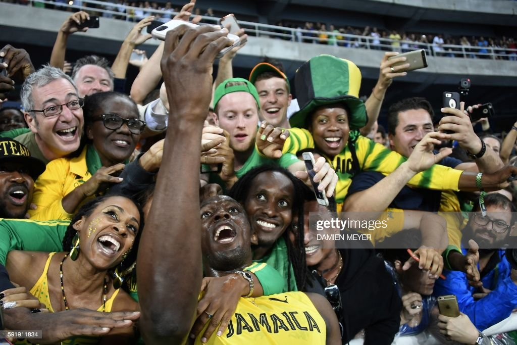 TOPSHOT Jamaica's Usain Bolt takes selfie photos as he celebrates with fans after winning the Men's 200m Final during the athletics event at the Rio...