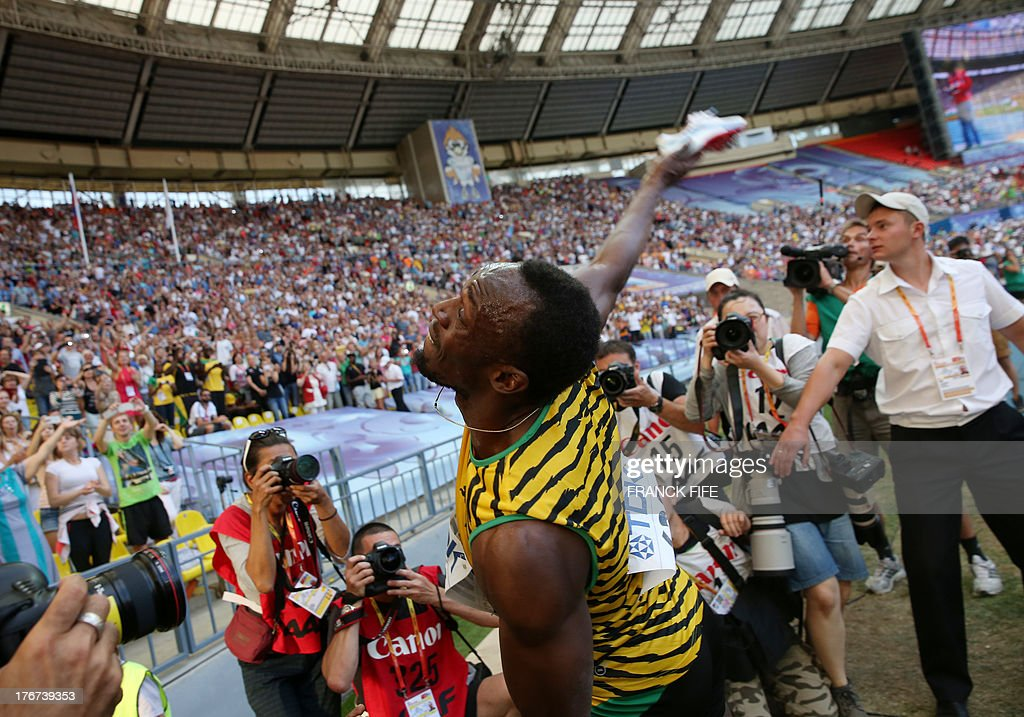 Jamaica's Usain Bolt throws his shoes after winning the men's 4x100 metres relay final at the 2013 IAAF World Championships at the Luzhniki stadium in Moscow on August 18, 2013. AFP PHOTO / FRANCK FIFE