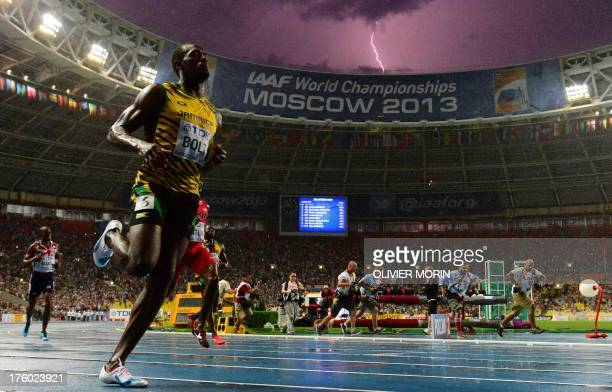 Jamaica's Usain Bolt wins the 100 metres final at the 2013 IAAF World Championships at the Luzhniki stadium in Moscow on August 11 2013 while a...