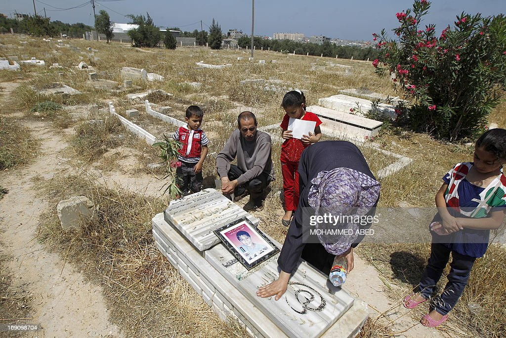 Jamal al-Dura and his children looks on as his wife washes down the grave stone of their son Mohammed, at the Bureij cemetery in the central of Gaza Strip, on May 20, 2013. Mohammed died in the arms of his father on September 30, 2000, after being caught in crossfire between Israeli soldiers and Palestinian militants at the start of the second intifada, or uprising. Israel said on May 19, 2013, that a France 2 television report seen worldwide on the death of Mohammed was 'baseless', following an analysis of the raw footage.