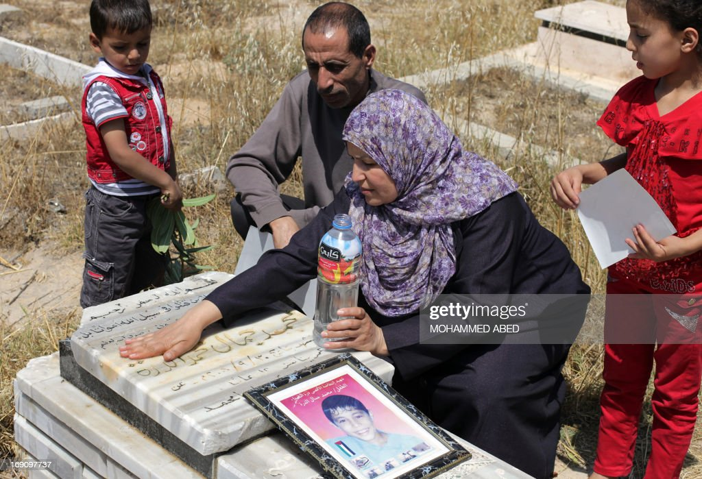 Jamal al-Dura and his family, clean grave of their son Mohammed, at the Bureij cemetery in the central of Gaza Strip, on May 20, 2013. Mohammed died in the arms of his father on September 30, 2000, after being caught in crossfire between Israeli soldiers and Palestinian militants at the start of the second intifada, or uprising. Israel said on May 19, 2013, that a France 2 television report seen worldwide on the death of Mohammed was 'baseless', following an analysis of the raw footage.