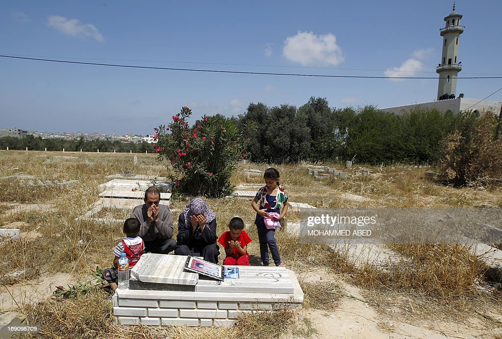 Jamal al-Dura and his family, pray over the grave of their son Mohammed, at the Bureij cemetery in the central of Gaza Strip, on May 20, 2013. Mohammed died in the arms of his father on September 30, 2000, after being caught in crossfire between Israeli soldiers and Palestinian militants at the start of the second intifada, or uprising. Israel said on May 19, 2013, that a France 2 television report seen worldwide on the death of Mohammed was 'baseless', following an analysis of the raw footage.