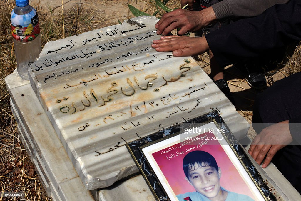 Jamal al-Dura (L) and his family, visit the grave of their son Mohammed, at the Bureij cemetery in the central of Gaza Strip, on May 20, 2013. Mohammed died in the arms of his father on September 30, 2000, after being caught in crossfire between Israeli soldiers and Palestinian militants at the start of the second intifada, or uprising. Israel said on May 19, 2013, that a France 2 television report seen worldwide on the death of Mohammed was 'baseless', following an analysis of the raw footage.