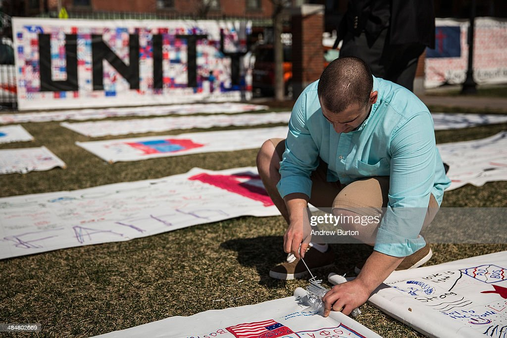 Jamal Alkattan pins down a corner of a memorial quilt prior to a flag raising ceremony at Boston Medical Center to commemorate the one year anniversary of the Boston marathon bombings on April 14, 2014 in Boston, Massachusetts. Last year, two pressure cooker bombs killed three and injured an estimated 264 others during the Boston marathon, on April 15, 2013.