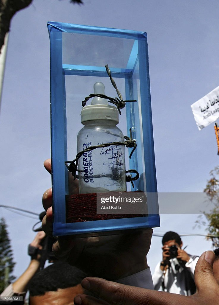 Jamal Al-Khodari, the head of the Peoples Committee, holds a baby bottle wrapped in barb-wire, before handing it to a United Nations envoy for Secretary-General Ban Ki-moon, as a symbolic expression of the suffering in Gaza, February 23, 2008 in Gaza city, Gaza Strip. Hundreds of Palestinians attended the demonstration, against the siege of Gaza, in front of the Gaza UN headquarters.