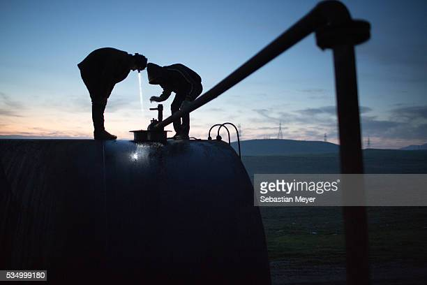 Jamal and Azdar watch as fuel oil is pumped into a storage drum at dawn Both boys were displaced from Sinjar by ISIS They now live next to an oil...