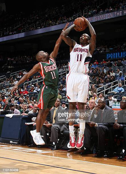 Jamal Crawford of the Atlanta Hawks shoots against Earl Boykins of the Milwaukee Bucks on March 15 2011 at Philips Arena in Atlanta Georgia NOTE TO...