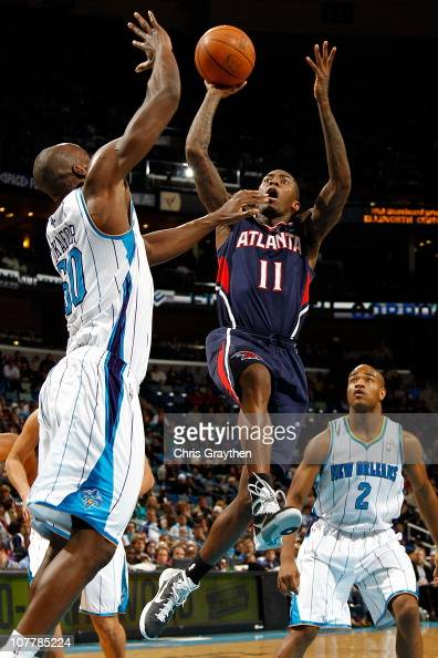 Jamal Crawford of the Atlanta Hawks shoots the ball over Emeka Okafor of the New Orleans Hornets at the New Orleans Arena on December 26 2010 in New...