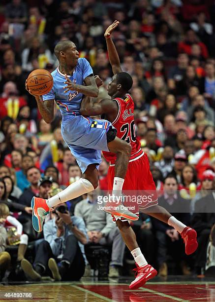 Jamal Crawford of the Los Angeles Clippers leaps to pass over Tony Snell of the Chicago Bulls at the United Center on March 1 2015 in Chicago...