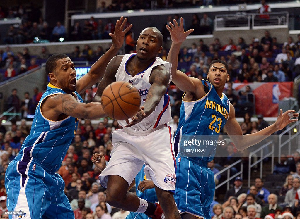 Jamal Crawford #11 of the Los Angeles Clippers makes a pass in front of Dominic McGuire #5 and Anthony Davis #23 of the New Orleans Hornets during a 93-77 Clipper victory for their 11th straight win at Staples Center on December 19, 2012 in Los Angeles, California.