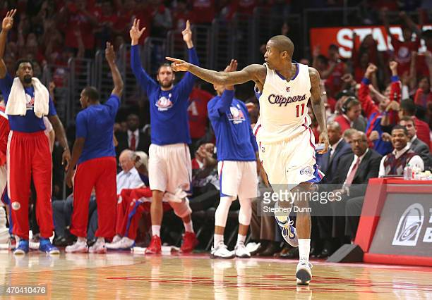 Jamal Crawford of the Los Angeles Clippers points after making a three point basket as teammates celebrate on the bench against the San Antonio Spurs...