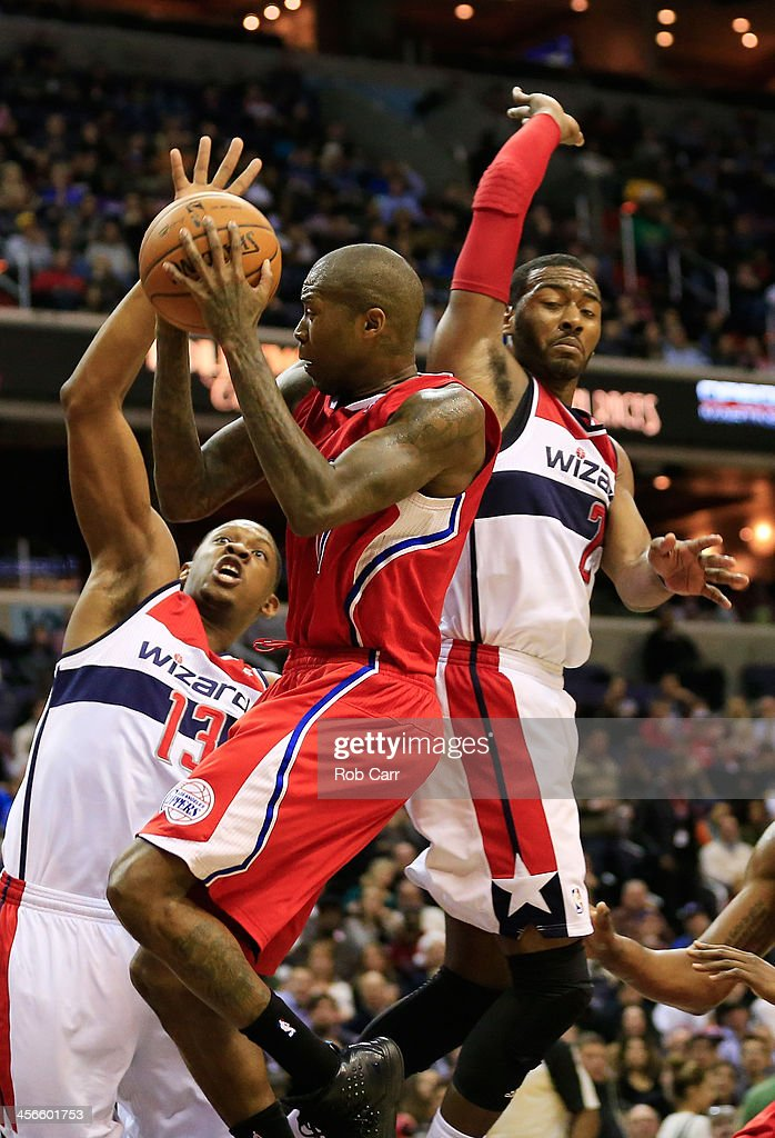 Jamal Crawford #11 of the Los Angeles Clippers puts up a shot between Kevin Seraphin #13 and John Wall #2 of the Washington Wizards during the second half at Verizon Center on December 14, 2013 in Washington, DC.