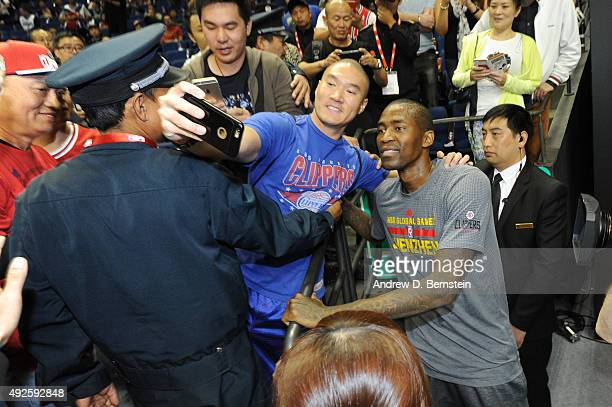 Jamal Crawford of the Los Angeles Clippers takes a photo with a fan before a game against the Charlotte Hornets as part of the 2015 NBA Global Games...