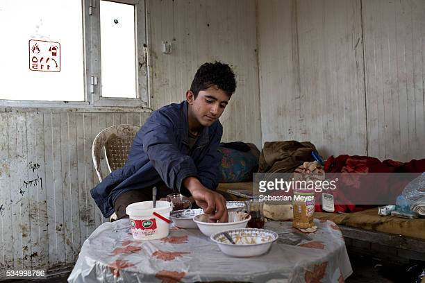 Jamal eats breakfast in the utility cabin Jamal a Yezidi boy from Sinjar lives with his displaced family next to an oil refinery in the Kurdish...