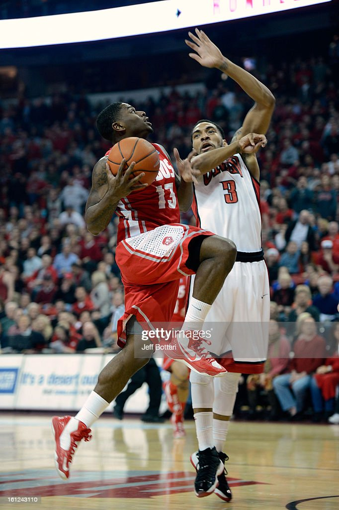 Jamal Fenton #13 of the New Mexico Lobos drives to the basket against Anthony Marshall #03 of the UNLV Rebels at the Thomas & Mack Center on February 9, 2013 in Las Vegas, Nevada.