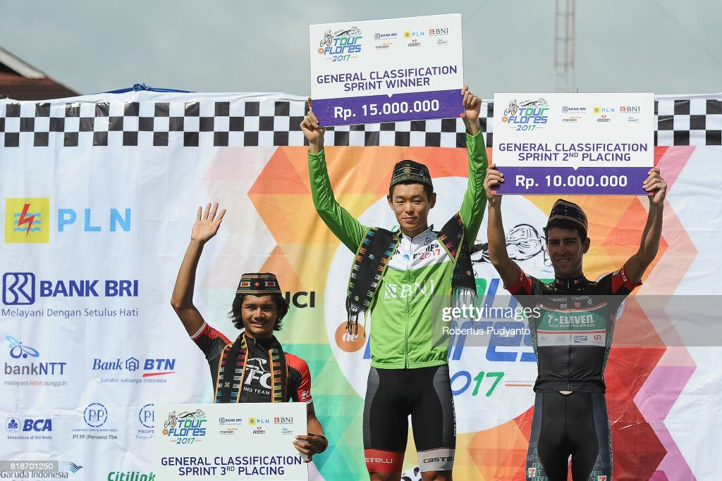 Jamal Hibatullah of KFC Cycling Team Indonesia (third position), green jersey winner Hyeongmin Choe of Geumsan Insam Cello Korea, and Edgar Nohales Nieto of 7 Eleven Cycling Team Philippines (runner-up) celebrate on the podium during Best Sprinters Classification awarding ceremony of the Tour de Flores 2017 on July 19, 2017 in Labuan Bajo, Flores, Indonesia.