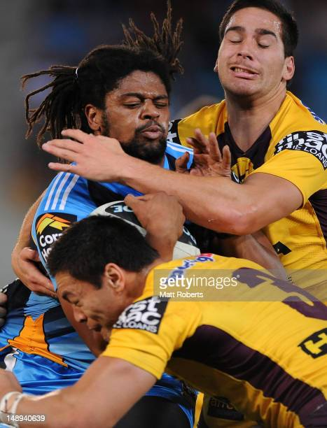 Jamal Idris of the Titans is tackled during the round 20 NRL match between the Gold Coast Titans and the Brisbane Broncos at Skilled Park on July 20...