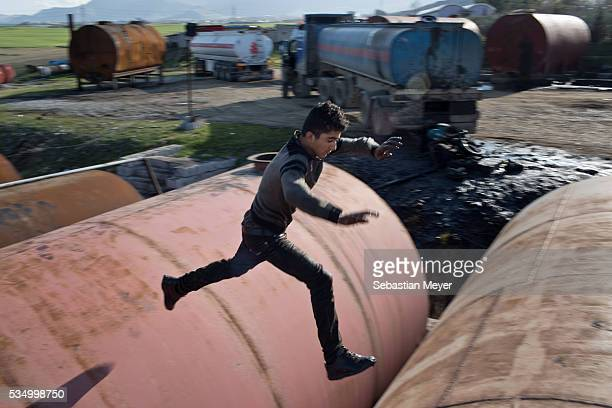 Jamal jumps between large storage drums at the refinery Jamal a Yezidi boy from Sinjar lives with his displaced family next to an oil refinery in the...
