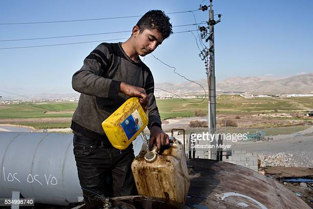 Jamal pours gasoline from a large drum into a jerry can Jamal a Yezidi boy from Sinjar lives with his displaced family next to an oil refinery in the...