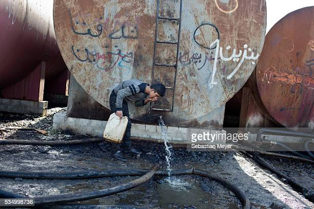 Jamal smells petrol coming out of a container to test it for its water content Jamal a Yezidi boy from Sinjar lives with his displaced family next to...