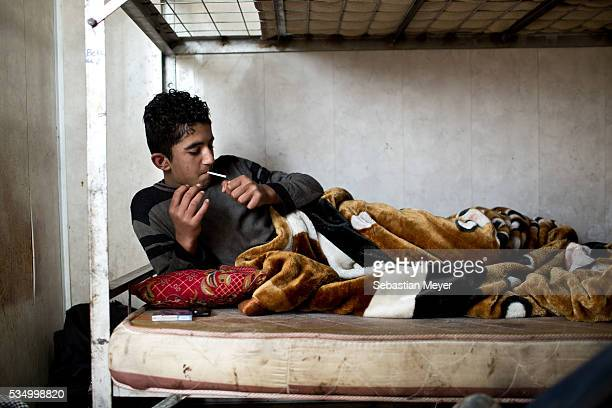 Jamal smokes a cigarette in his bunkbed Jamal a Yezidi boy from Sinjar lives with his displaced family next to an oil refinery in the Kurdish Region...