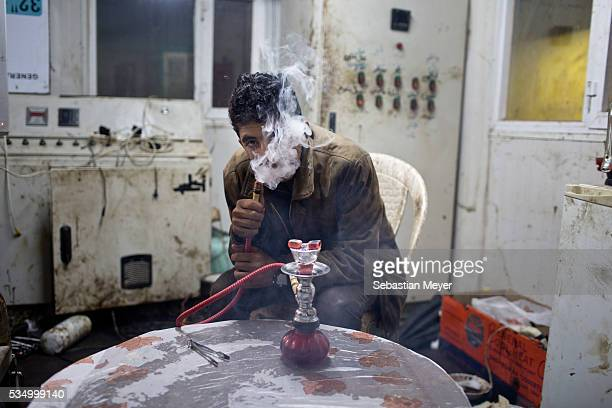 Jamal smokes flavored tobacco from a small hookah pipe inside the utility cabin The family of Yezidis displaced from Sinjar live next to an oil...