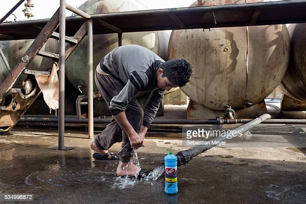 Jamal washes his feet in the refinery after playing in dirty water on the banks of the Tanjero river Jamal a Yezidi boy from Sinjar lives with his...
