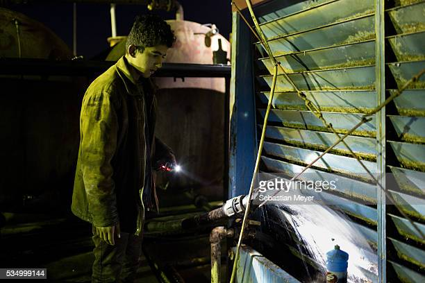 Jamal watches as he pumps water into the cooling bank at the refinery The family of Yezidis displaced from Sinjar live next to an oil refinery in the...