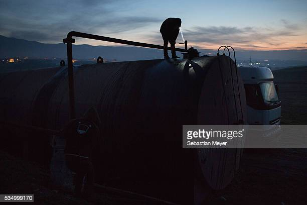 Jamal watches fuel oil pour into a storage drum at dawn The family of Yezidis displaced from Sinjar live next to an oil refinery in the Kurdish...