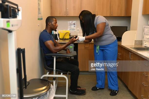 Jamal Wilson has blood drawn from a finger as he receives a free HIV test from a medical assistant on National HIV Testing Day at a Planned...