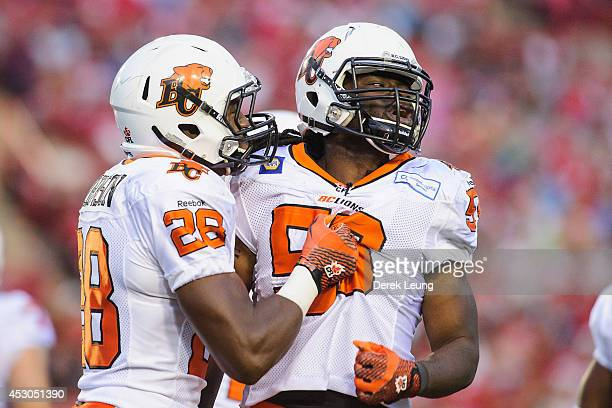 Jamall Johnson and Solomon Elimimian of the BC Lions celebrate after a play against the Calgary Stampeders during a CFL game at McMahon Stadium on...