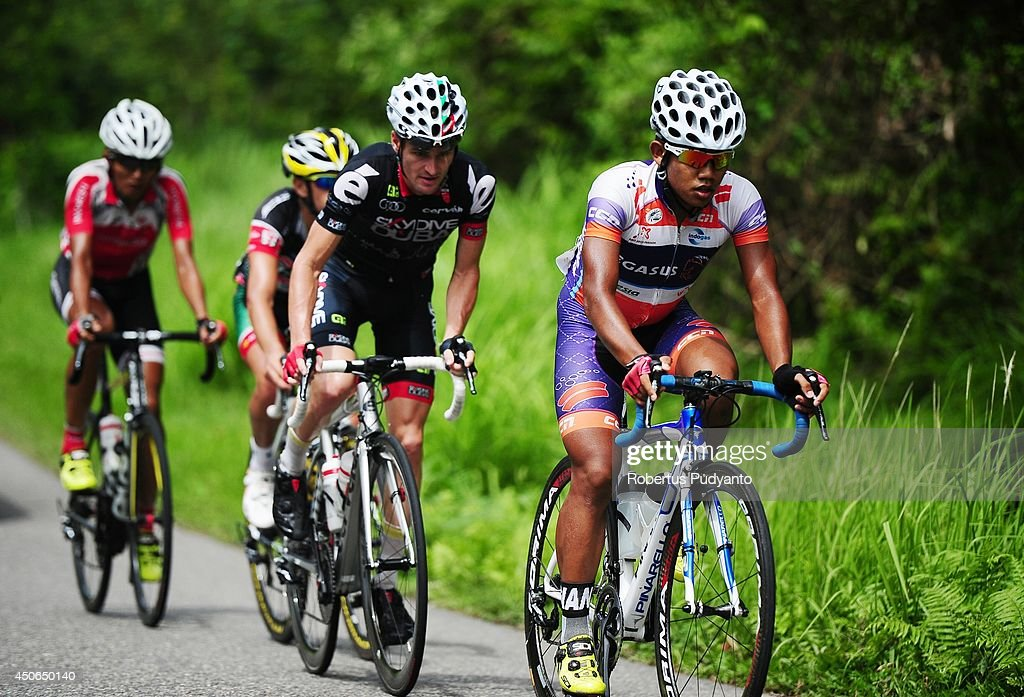 Jamalldin Novardianto of Pegasus Continental Cycling Team Indonesia leads follow by Oscar Pujol Munoz of Skydive Dubai Pro Cycling Team, Edgar Nohales Nieto of Team 7 Eleven Roadbike Phillipine, and Hari Fitriyanto of Indonesia National Team during stage 9 of the 2014 Tour de Singkarak from Pesisir Selatan to Padang City with a distance of 120.5 km on June 15, 2014 in Padang, Indonesia.