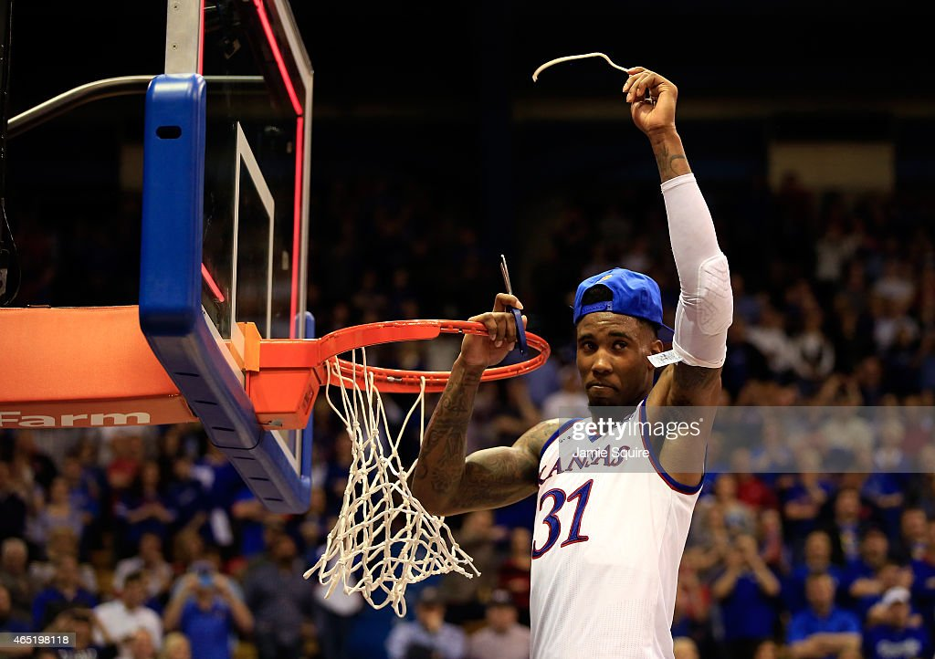 Jamari Traylor of the Kansas Jayhawks cuts down the net after the Jayhawks defeated the West Virginia Mountaineers 7669 in overtime to win the game...