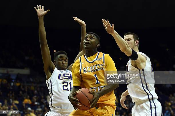 Jamaya Burr of the McNeese State Cowboys drives between Aaron Epps and Darcy Malone of the LSU Tigers during the second half of a game at the Pete...