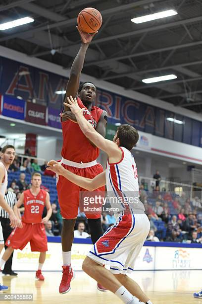 Jameel Warney of the Stony Brook drives to the basket over Jesse Reed of the American University Eagles during a college basketball game at Bender...