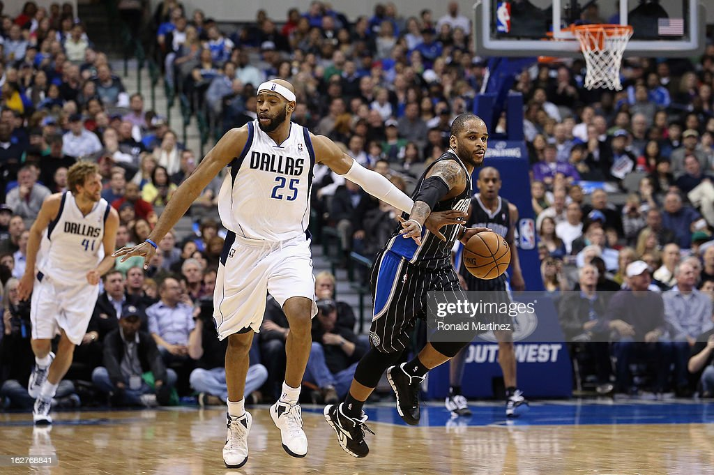 Jameer Nelson #14 of the Orlando Magic dribbles the ball past Vince Carter #25 of the Dallas Mavericks at American Airlines Center on February 20, 2013 in Dallas, Texas.